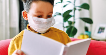 School boy reading book with mask